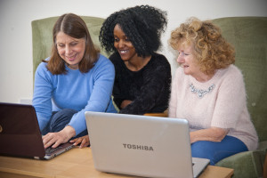 HCHA tenants Charlotte Smyth (left) and Sylvia Thornton (right) with Sylvia Njunge (middle) using their own computers at Paxfold.